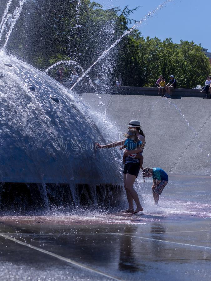 Mutter und Kind am Berühren von Seattle-Brunnen stockbild