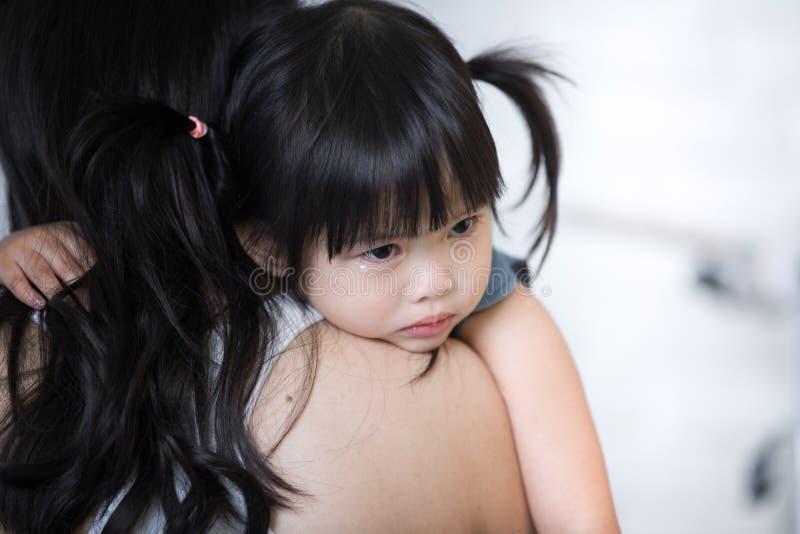 Mutter und Kind, das nette kleine Mädchen, das auf ihrem Mutter ` s sollten stillsteht stockfoto