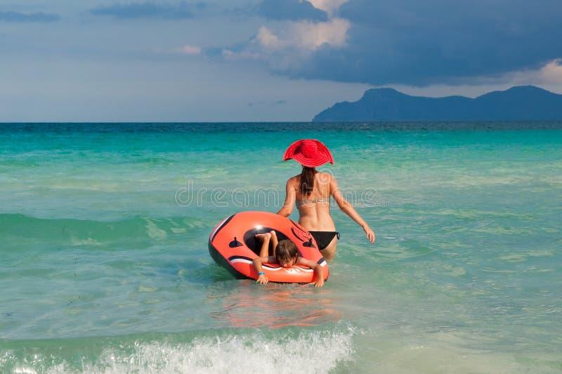 Mutter und Kind, die in den Wellen spielen lizenzfreies stockfoto