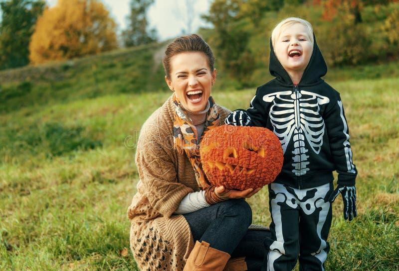 Mutter und Kind, die Halloween-Kürbis Jack Oâ €™Lantern zeigt lizenzfreies stockfoto