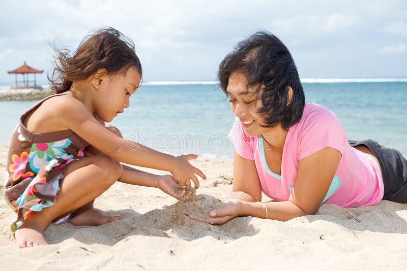 Mutter und Kind, die mit Strandsand spielen stockbild