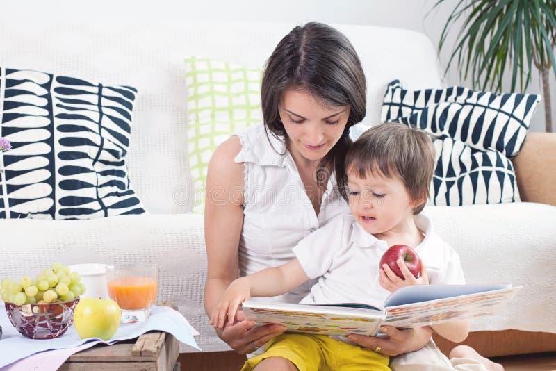 Mutter und Kind, ein Buch lesend und essen Früchte lizenzfreies stockbild