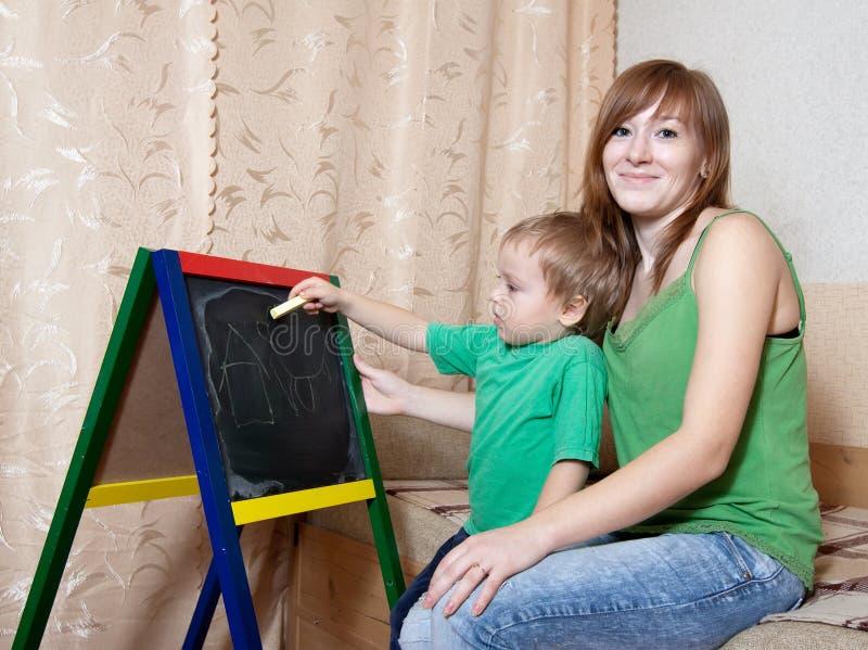 Mutter und Kind zeichnet auf Tafel stockbild