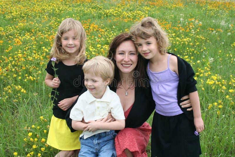 Mutter und Kinder auf dem Blumen-Gebiet lizenzfreie stockfotos