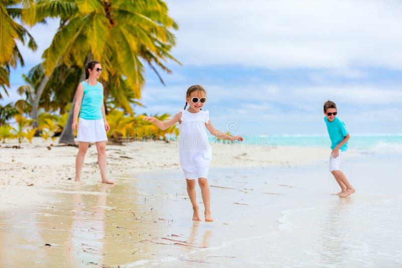 Mutter und Kinder auf einem tropischen Strand stockbild