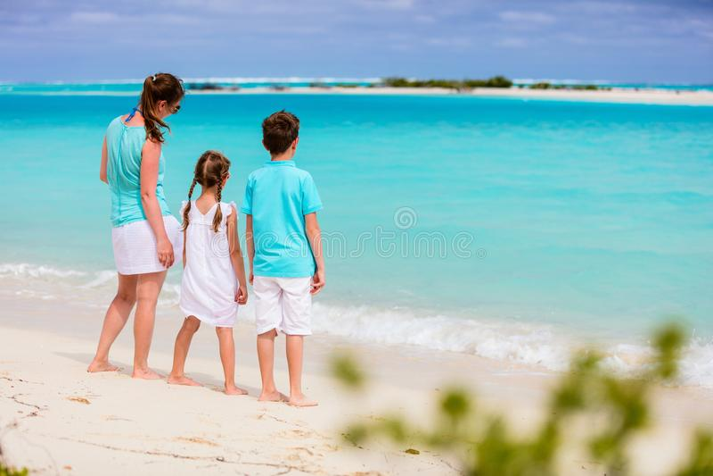 Mutter und Kinder auf einem tropischen Strand lizenzfreie stockbilder