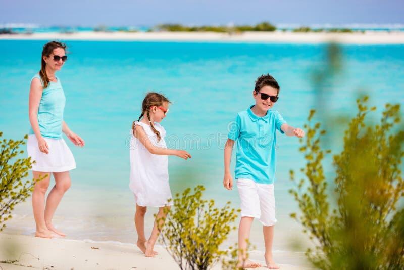 Mutter und Kinder auf einem tropischen Strand stockfotografie