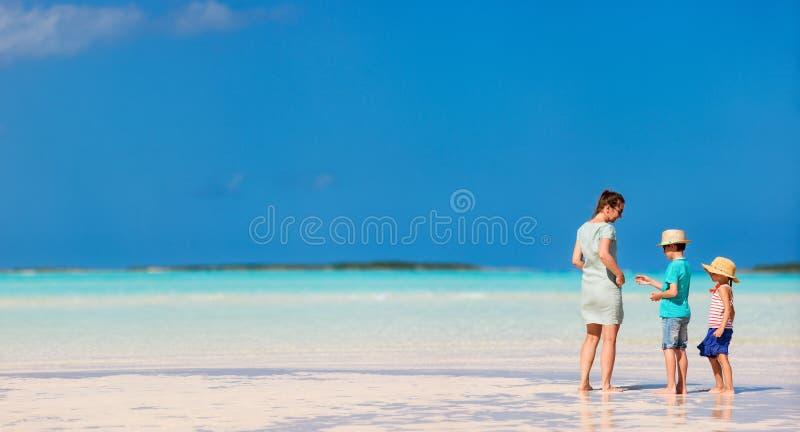 Mutter und Kinder auf einem tropischen Strand lizenzfreie stockfotos