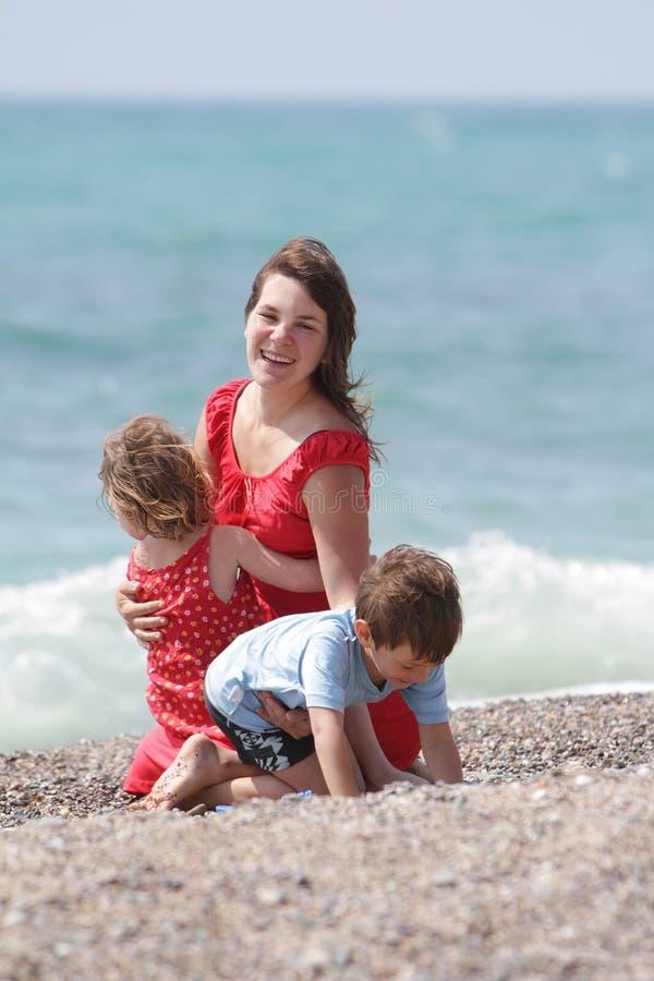 Mutter und Kinder auf Seehintergrund stockbilder