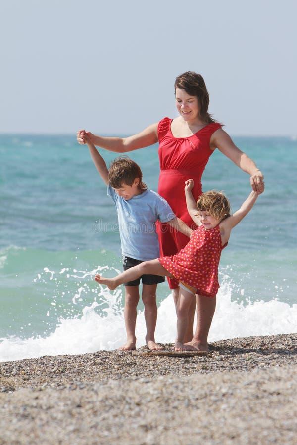 Mutter und Kinder auf Seehintergrund stockfoto