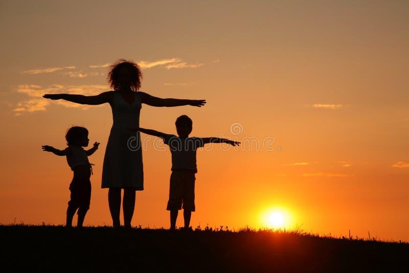 Mutter und Kinder auf Sonnenuntergangsporttraining stockbilder