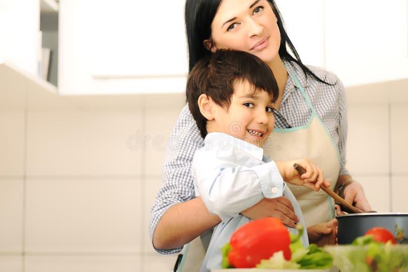 Mutter und Kinder bereiten a-Mahlzeit vor lizenzfreies stockfoto