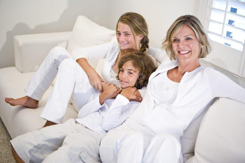 Mutter und Kinder, die auf weißem Sofa sich entspannen lizenzfreies stockbild