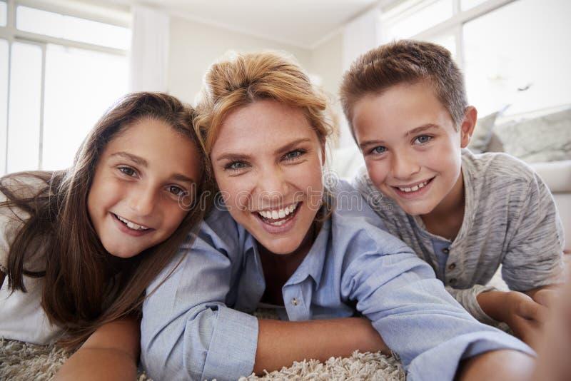 Mutter und Kinder, die auf Wolldecke liegen und zu Hause für Selfie aufwerfen lizenzfreie stockbilder