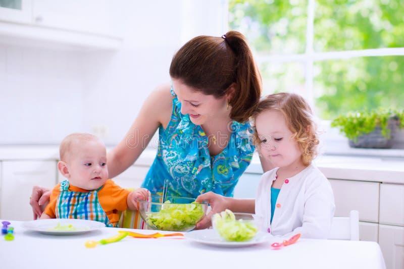 Mutter und Kinder, die in einer weißen Küche kochen stockbild
