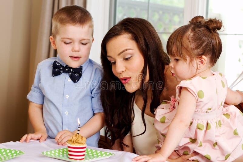 Mutter und Kinder, die heraus Kerze durchbrennen lizenzfreie stockfotografie