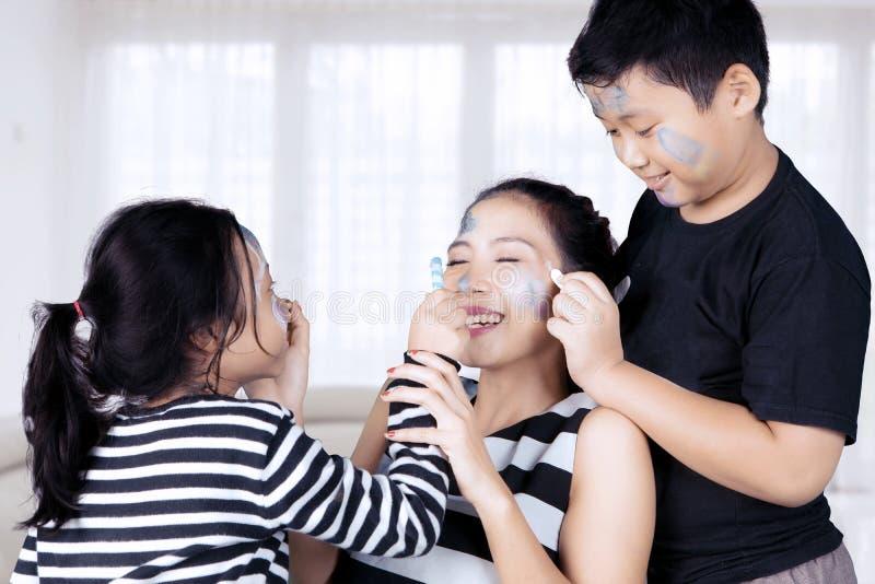 Mutter und Kinder, die mit Gesichtsmalerei spielen stockfotos