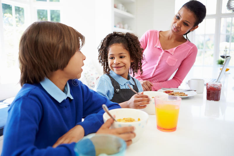 Mutter und Kinder, die vor Schule frühstücken stockbilder