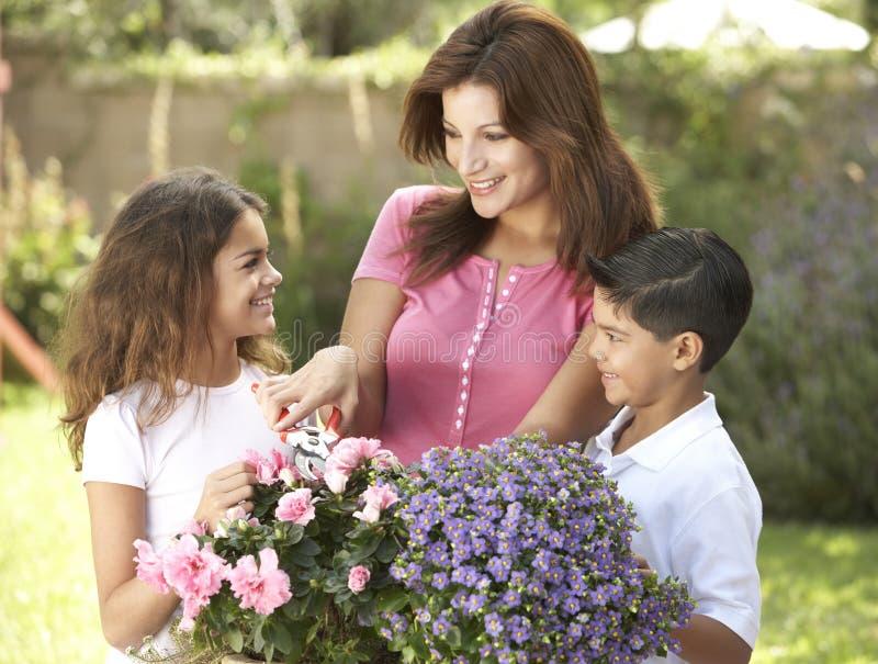 Mutter und Kinder, die zusammen im Garten arbeiten lizenzfreies stockbild