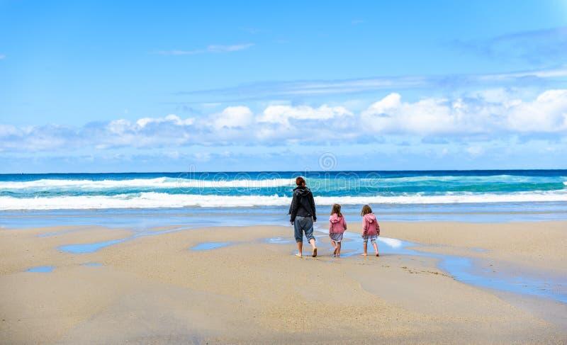 Mutter und Kinder gehen auf sandigen atlantischen Strand lizenzfreies stockbild