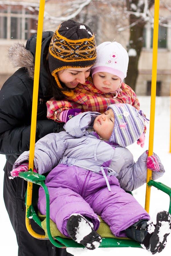 Mutter und Kinder im Schwingen im Winter lizenzfreie stockfotos