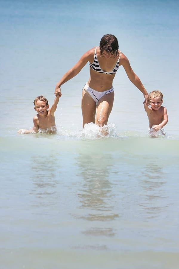 Mutter und Kinder im Wasser stockfotos
