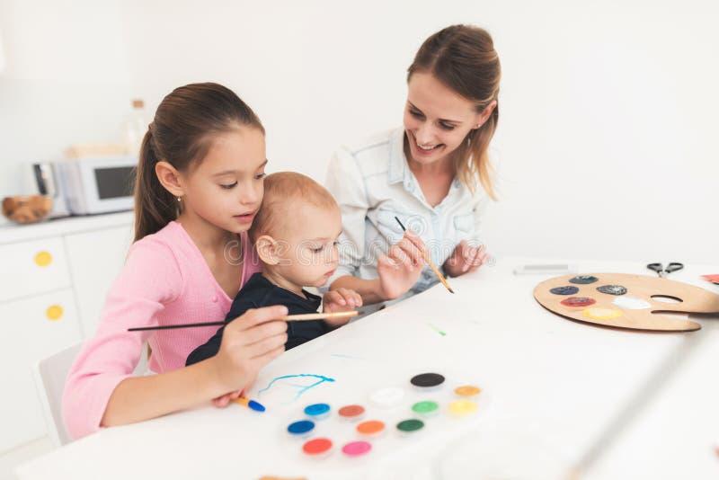 Mutter und Kinder nehmen an Zeichnung teil Sie haben Spaß in der Küche Das Mädchen hält ihren jüngeren Bruder in ihr lizenzfreie stockfotos