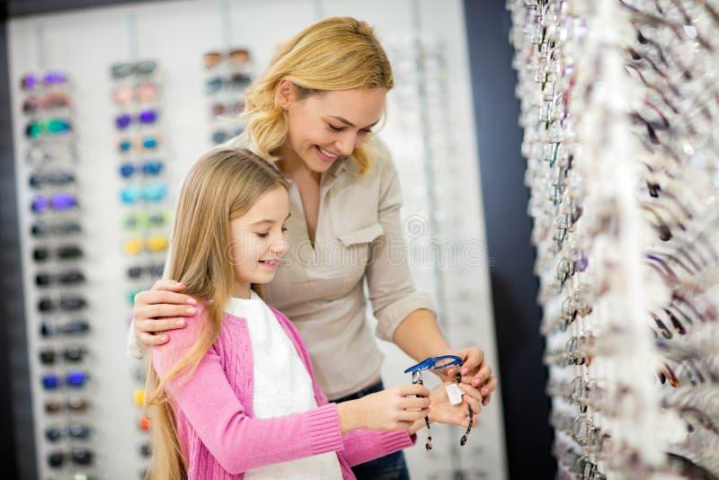 Mutter- und Kinderblick auf blauen Rahmen für Brillen lizenzfreie stockfotografie