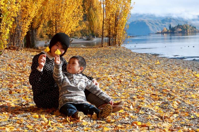 Mutter-und Kinderjungen-Sohnspiele in gefallenen Blättern lizenzfreie stockfotografie