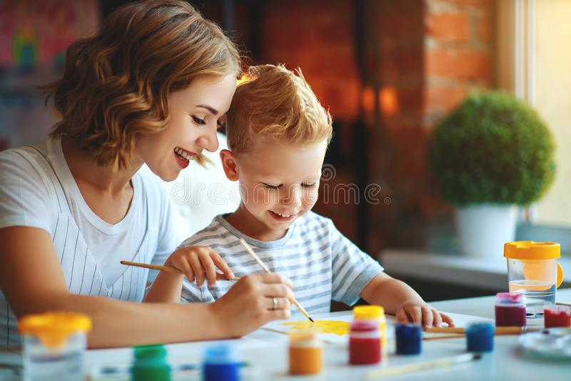 Mutter- und Kindersohnmalerei zeichnet in Kreativität im Kindergarten lizenzfreie stockfotos