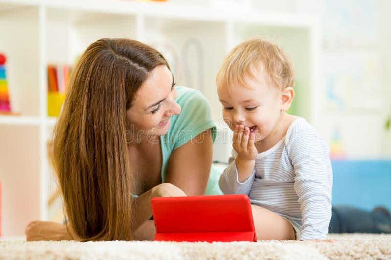 Mutter- und Kinderspiel am Tablet-Computer stockfotografie