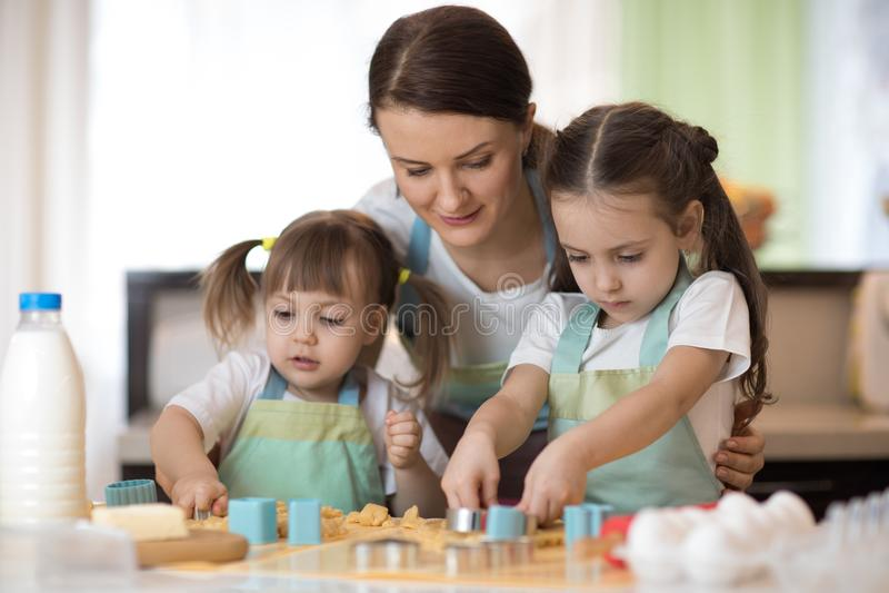 Mutter- und Kindertöchter in der Küche, die Plätzchen macht lizenzfreie stockbilder