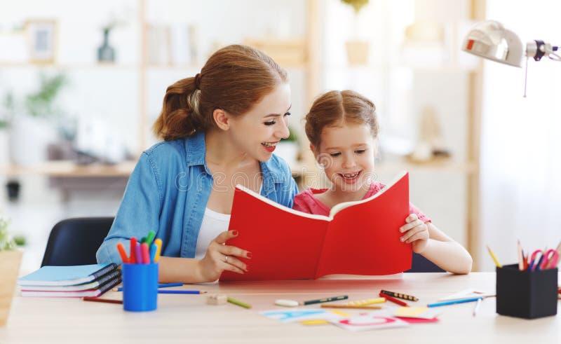Mutter- und Kindertochter, die zu Hause Hausarbeitschreiben und -lesung tut stockbilder