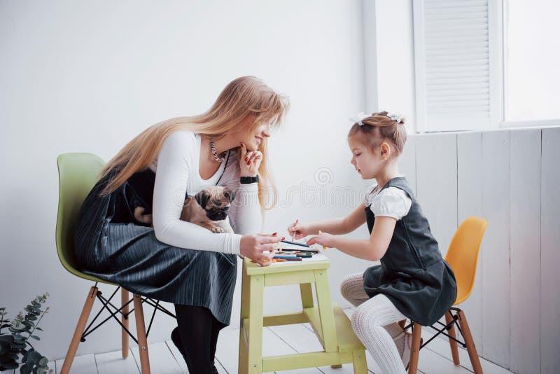 Mutter- und Kindertochter zeichnet teilnehmen an Kreativität im Kindergarten kleiner Pug mit ihnen lizenzfreie stockfotos