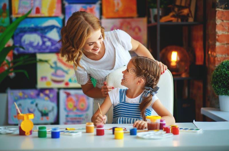Mutter- und Kindertochtermalerei zeichnet in Kreativität im Kindergarten stockfotografie