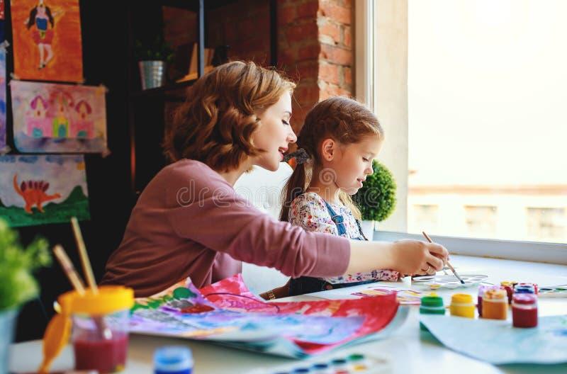 Mutter- und Kindertochtermalerei zeichnet in Kreativität im Kindergarten stockbild
