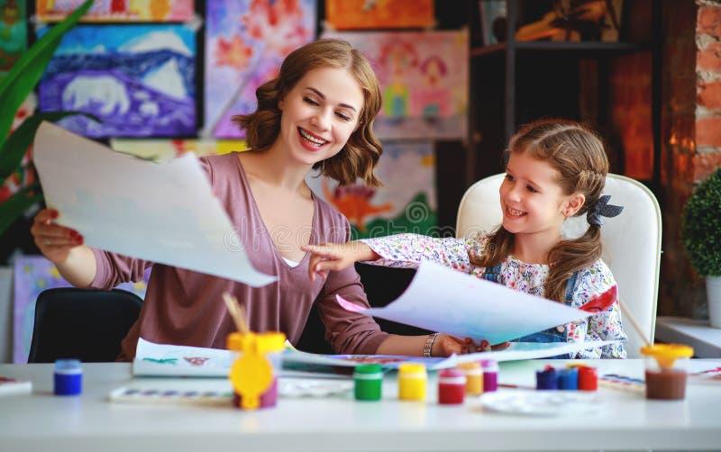 Mutter- und Kindertochtermalerei zeichnet in Kreativität im Kindergarten lizenzfreie stockfotografie