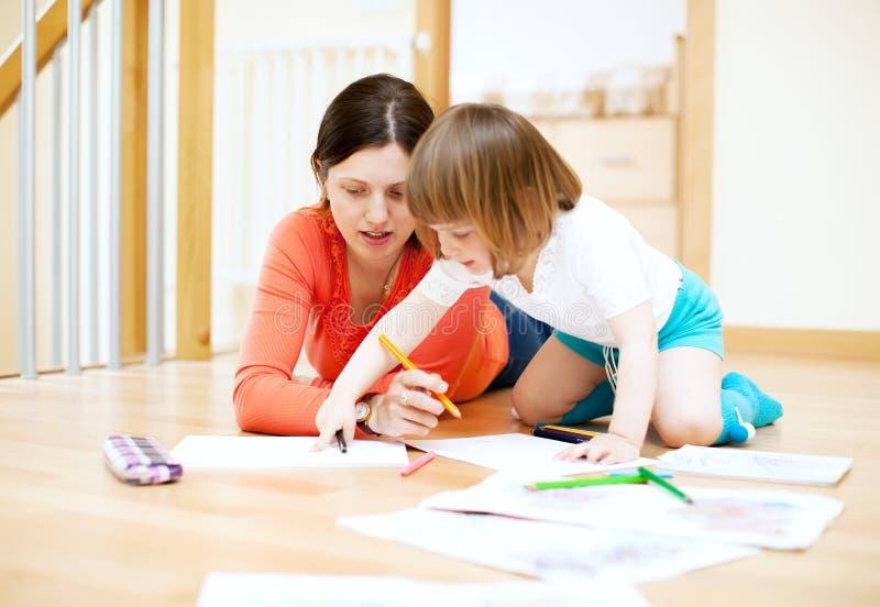 Mutter- und Kinderzeichnung auf Papier. Fokus auf nur Frau stockfotografie
