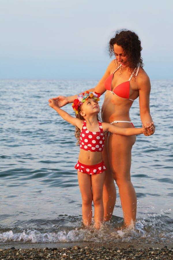 Mutter und kleine Tochter, die auf Strand stehen stockfotografie