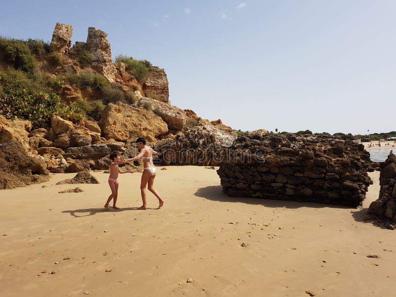 Mutter und kleine Tochter, die Spaß auf dem Strand haben lizenzfreie stockfotos