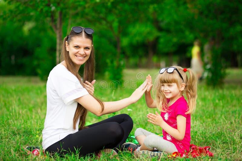 Mutter und kleine Tochter, die zusammen im Park spielen Porträt im Freien der glücklichen Familie Glückliche Mutter ` s Tagesfreu stockfotografie