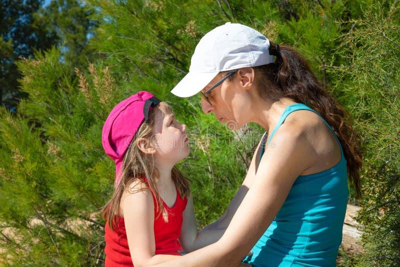 Mutter und kleine Tochter mit Kappen Sitzen in der Landschaft sprechend stockbilder