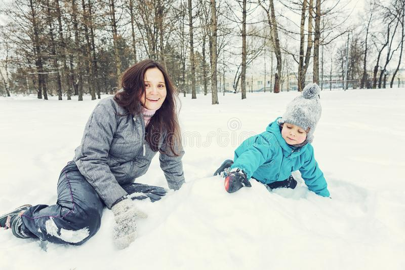 Mutter und kleiner Sohn, die im Schnee spielen stockfotos