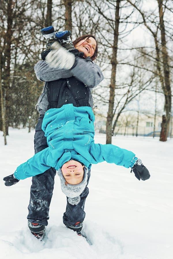 Mutter und kleiner Sohn, die im Schnee spielen stockfoto