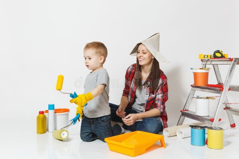 Mutter und kleiner Sohn mit Instrumenten für den Erneuerungswohnungsraum lokalisiert auf weißem Hintergrund Tapete, klebend lizenzfreie stockfotos