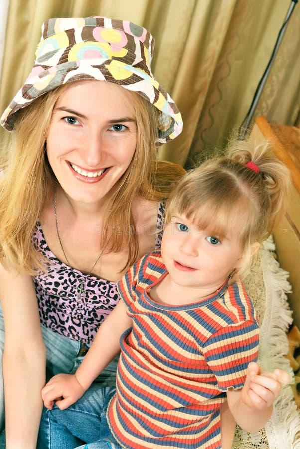 Mutter und kleines Mädchen auf ihren Knien stockfoto