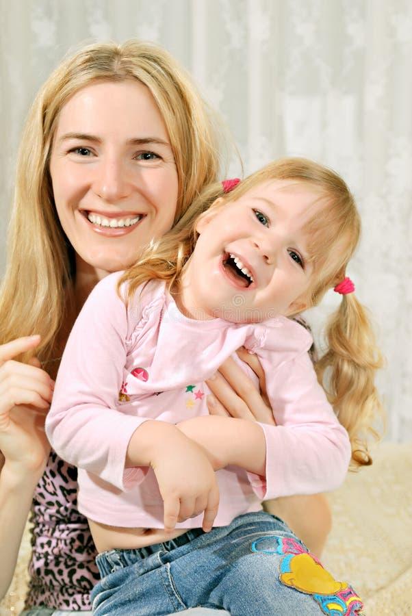 Mutter und kleines Mädchen auf ihren Knien lizenzfreie stockfotografie