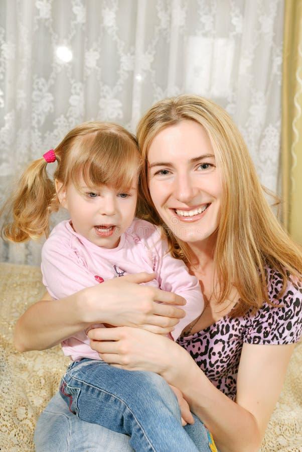 Mutter und kleines Mädchen auf ihren Knien stockbild