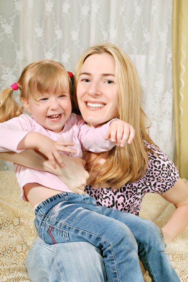 Mutter und kleines Mädchen auf ihren Knien lizenzfreies stockbild