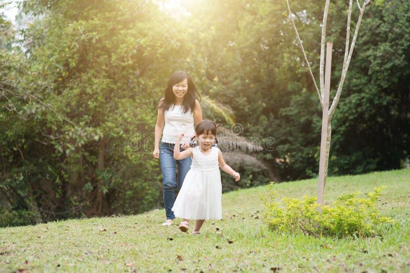 Mutter und kleines Mädchen, die draußen jagen lizenzfreies stockbild